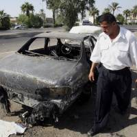 An Iraqi traffic policeman inspects a car destroyed in an incident involving a Blackwater security detail in Baghdad's Nisoor Square in September 2007. | AP