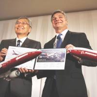 Hideaki Omiya, chairman of Mitsubishi Heavy Industries Ltd. and Japan Aircraft Development Corp., and Ray Conner, CEO of Boeing Commercial Airplanes, show a memorandum of agreement for manufacturing the 777X passenger jet during a news conference in Tokyo on Thursday. | REUTERS