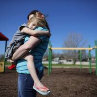 Andrea Smith carries Norah, one of her daughters, at a public playground in Winthrop Harbor, Illinois, on May 9. | REUTERS