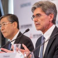 Shunichi Miyanaga, chief executive officer of Mitsubishi Heavy Industries, and Joe Kaeser, CEO of Siemens, hold a news conference in Paris on Tuesday to announce a joint bid for Alstom SA. | BLOOMBERG