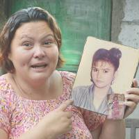 Beirut Calaguas holds up a photo of herself when she was 17 years old during an interview at the end of May in Angeles.   AFP-JIJI