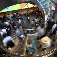 Customers descend a spiral staircase during the opening ceremony of Apple Inc.'s Omotesando store in Tokyo on June 13. Consumer prices in May climbed at their fastest pace in 32 years, swelled by April's consumption tax increase, government data showed Friday.  | BLOOMBERG