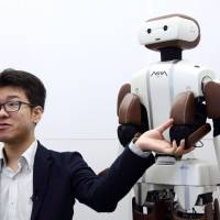 Wataru Yoshizaki, chief robot officer of Asratec Corp., speaks Tuesday next to the company's humanoid robot, Asra C1, in Tokyo. | BLOOMBERG