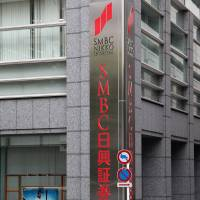 A pedestrian walks by the headquarters of SMBC Nikko Securities Inc. in Tokyo. | BLOOMBERG