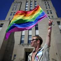 Gary Jones, 37, holds a rainbow-striped gay and lesbian pride flag in front of Racine County Courthouse during a march in Racine, Wisconsin, on Friday. | AP