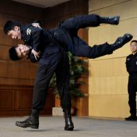 Police demonstrate defensive skills during an anti-terrorism lecture at the University of International Business and Economics in Beijing last Wednesday. China has vowed to wage a crackdown on terrorism in restive western Xinjiang region. | AFP-JIJI