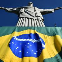 A Brazilian flag covers the base of the 'Christ the Redeemer' statue in Rio de Janeiro on Thursday. | AFP-JIJI