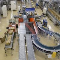 Asahi Soft Drinks Co. employees work on the production line at the company's Mount Fuji factory in Fujinomiya, Shizuoka Prefecture, in March. | BLOOMBERG