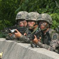 South Korean soldiers on Monday aim their machine guns during the hunt for a fellow soldier suspected of killing five of his comrades in Goseong, South Korea, last Saturday. | AP