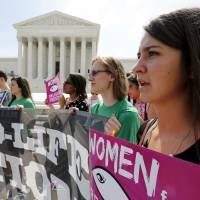 Pro-life protesters rally outside the Supreme Court in Washington on Thursday as the court deliberated on a Massachusetts law that mandated a no-protest buffer zone around abortion clinics. | REUTERS