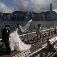 A couple takes wedding photos against the backdrop of Hong Kong's business district on Wednesday. The city will hold a controversial 'referendum' on democracy on Friday, a prelude to an escalating campaign of dissent that could shut down the former British colony's financial district and further anger Communist Party leaders in mainland China. | REUTERS
