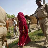 The mother of one of two teenage girls who were raped and murdered is seen with police last Saturday. | REUTERS
