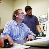 Kurt Sickfus, a professor at the University of Tennessee (seated), works with Ph.D. student Devin Roberts on the Scanning Electron Microscope in Knoxville, Tennessee, on June 2. Sickfus is among several researchers involved in efforts to make 'accident-resistant' fuel for the nuclear industry. | AP
