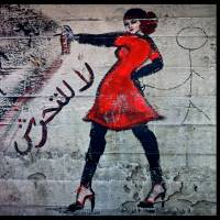 Graffiti of a woman with the words 'no harassment' written in Arabic script is seen in June 2012 (left) in the upscale Zamalek neighborhood in Cairo, and after the picture was defaced in November of that year with a crude stick figure touching her backside. | AP