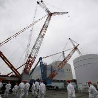 Members of the media and Tepco employees head toward the reactor 1 building at the Fukushima No. 1 nuclear plant on March 10. | POOL