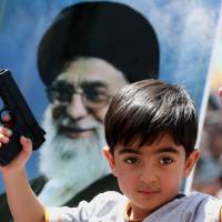 An Iraqi boy living in Iran holds a toy gun and flashes a victory sign in front of a poster of the Iranian Supreme leader Ayatollah Ali Khamenei in a demonstration against Sunni militants of the al-Qaida-inspired Islamic State of Iraq and Syria and to support the Grand Ayatollah Ali al-Sistani, Iraq's top Shiite cleric, in Tehran on Friday. | AP