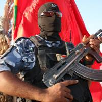 A masked Iraqi Shiite fighter holds his weapon during a rally in support of the nation's security forces in the southern city of Basra on Monday. | AFP-JIJI