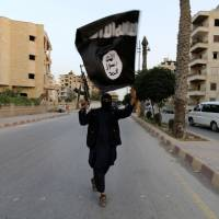 A member of the Islamic State of Iraq and the Levant (ISIL) waves the group's flag in Raqqa, Syria, on Sunday. The group, which has captured vast tracts of territory in Iraq and Syria, has declared itself an Islamic caliphate and called on factions worldwide to unite behind its leader, Abu Bakr al-Baghadi. | REUTERS