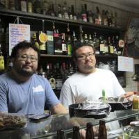 William Takahiro Higuchi (left) and Wagner Yoshihiro Higuchi tend the Bar Kintaro in Sao Paulo on June 10. Brazil hosts the world's largest ethnic Japanese population outside Japan — 1.5 million, or half of the roughly 3 million scattered around the globe. Many of these so-called 'Nikkei' have found themselves caught in the crevice between two cultures, and have struggled to gain acceptance in either. | AP