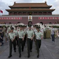 Paramilitary policemen march out of Tiananmen Gate to clear tourists from the area for a May 28 flag-lowering ceremony at Tiananmen Square in Beijing.   AP