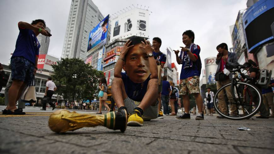 A soccer fan wearing a mask of Japan's Yuto Nagatomo holds his head in his hands next to a mock World Cup trophy in Tokyo's Shibuya Ward after the Samurai Blue were defeated 4-1 in their World Cup match against Colombia on Tuesday.