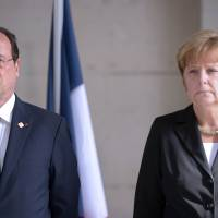 French President Francois Hollande (left) and German Chancellor Angela Merkel stand Thursday during a ceremony to mark the 100th anniversary of the outbreak of World War I in Ypres, Belgium. | AFP-JIJI