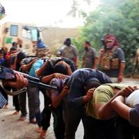 This image posted to a militant website Saturday appears to show Islamic State of Iraq and Syria militants leading away captured Iraqi soldiers dressed in plainclothes after taking over a base in Tikrit. The Islamic militant group that seized much of northern Iraq has posted photos that appear to show its fighters shooting dead dozens of captured Iraqi soldiers in a province north of Baghdad. | AP