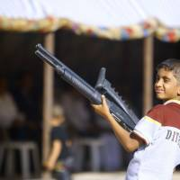 An Iraqi boy holds a weapon Tuesday as he takes part in a gathering of Shiite tribesman showing their willingness to join Iraqi security forces in the fight against ISIS jihadi militants who have taken over several cities in northern Iraq. | AFP-JIJI