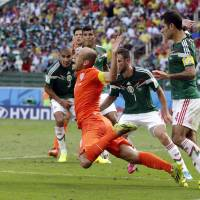 The tipping point: The Netherlands' Arjen Robben wins a critical penalty as he falls during his team's match against Mexico on Sunday. The Dutch won 2-1. | AP