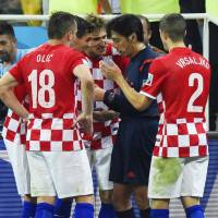 See no evil: Croatian players plead their case after referee Yuishi Nichimura (center) awarded Brazil a controversial penalty in the 71st minute on Thursday in Sao Paulo. | KYODO