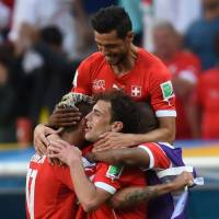 Never say never: Swiss players celebrate after scoring a goal against Ecuador during their match at the 2014 World Cup on Sunday in Brasilia. Switzerland rallied from a goal down to win 2-1. | AFP-JIJI