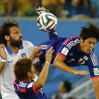 Japan's Atsuto Uchida (right) is fouled by Giorgios Samaras of Greece during their Group C match Thursday in Natal, Brazil, in the 2014 World Cup. | REUTERS