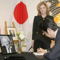 Prime Minister Shinzo Abe signs the condolence book for former Ambassador Howard Baker at the U.S. Embassy in Tokyo on Monday as current Ambassador Caroline Kennedy looks on. | KYODO