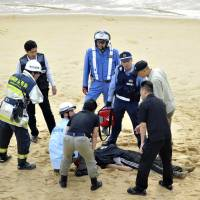 Police officers surround Yasuyuki Okuma, who was found lying on a beach in the city of Fukuoka on Monday morning after escaping from a hospital where he had been held for psychiatric evaluations earlier in the day. | KYODO