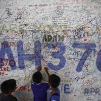 Children write messages of hope for the passengers of missing Malaysia Airlines Flight MH370 at Kuala Lumpur International Airport on Friday. Sunday marked 100 days since the plane disappeared. | REUTERS