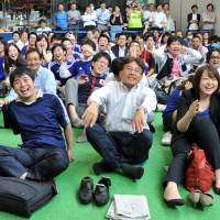 Fans groan in disappointment as they follow the Group C match between Japan and Greece at an office block near Tokyo Station on Friday morning. The final score was 0-0, likely ending Japan's hopes of advancing in the World Cup. | YOSHIAKI MIURA