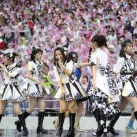 Members of AKB48 perform during the all-girl pop idol group's annual popularity poll extravaganza in Tokyo on Saturday, a month after two members were attacked by a saw-wielding assailant. Mayu Watanabe was voted the top AKB48 idol and will lead the group for the next year. | AP