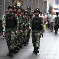 Paramilitary policemen patrol a street in Shenzhen, Guangdong province, on May 27. China has announced a year-long anti-terrorism operation in Xinjiang, home to a large Muslim Uighur minority, as well as nationwide, following a series of bloody attacks that Beijing blames on Islamists and separatists from the region. | REUTERS