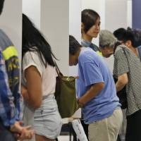 People vote at a polling station for an unofficial referendum on democratic reform in Hong Kong on Sunday. More than 700,000 Hong Kongers had voted as of early Monday, dwarfing the most-optimistic forecasts by organizers. | AP