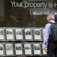 A pedestrian stands beneath a 'Your Property is HOT!' sign as he looks at leaflets about residential properties displayed for sale in the window of an estate agent in Guildford, England, on Monday. As Britons brace for the Bank of England to announce steps to restrain the housing market this week, Chief Secretary to the Treasury Danny Alexander dismissed talk of a bubble. | BLOOMBERG