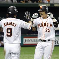 Offensive force: The Giants' Shuichi Murata, congratulated by teammate Yoshiyuki Kamei in the second inning, drove in four runs on Sunday against the Hawks. Yomiuri defeated Fukuoka Softbank 10-5.  | KYODO