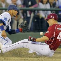 Made it: Tohoku Rakuten's John Bowker slides to third base before Yokohama's Yulieski Gurriel can make the catch during the Eagles' 10-0 win on Monday. | KYODO