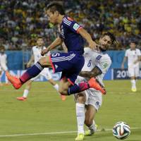 Up, up and away: Japan's Yuto Nagatomo leaps past Greece's Panagiotis Kone on Thursday in Natal, Brazil. | AP