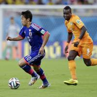 Back to the drawing board: Japan's Shinji Kagawa, chased by Cote d'Ivoire's Cheik Tiote during Saturday's World Cup Group C match, says his team's lack of aggressiveness was a big factor in the loss.  | AP