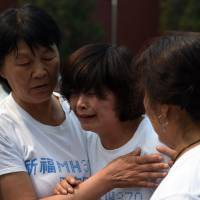Relatives of passengers on missing Malaysia Airlines Flight MH370 cry as they gather at the Lama Temple in Beijing on Sunday. Chinese relatives marked 100 days since the plane went missing on a flight from Kuala Lumpur to Beijing by offering prayers and burning incense at the Buddhist temple. | AFP-JIJI