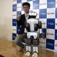 Wataru Yoshizaki, chief robot creator at Asratec, poses with a concept robot called Asra C1 at SoftBank's headquarters in Tokyo on Wednesday.  | KAZUAKI NAGATA