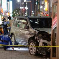 A wrecked car sits on the sidewalk after it struck pedestrians and smashed into a phone booth Tuesday evening in the bustling Ikebukuro district in Toshima Ward, Tokyo. | KYODO