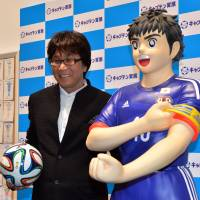 Illustrator Yoichi Takahashi (left) poses next to a figure of Captain Tsubasa, a fictional soccer player, at a preview of an exhibition on the cartoon character at a Tokyo museum Friday. The show, which will run until July 6, includes animated films and drawings, including one done for the World Cup in Brazil. | AFP-JIJI