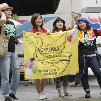 Activists rally outside the venue for Kyushu Electric Power Co.'s annual shareholders' meeting Thursday in Chuo Ward, Fukuoka, to protest plans to restart its suspended nuclear reactors. | KYODO