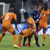 Crowded out: Keisuke Honda takes on the Cote d'Ivoire defense during Japan's 2-1 loss at the 2014 World Cup on Saturday. | AP